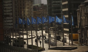 People walk past European Union flags placed outside the European Commission headquarters in Brussels, Thursday, March 14, 2019.