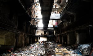 Suspended walkways and staircases block the lights, while refuse piles up and sewage drips from poorly-maintained pipes.