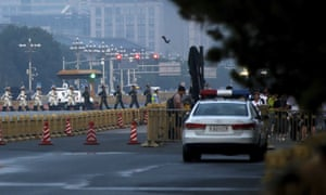 Policemen monitor people as a Chinese honour guard marches across a street after the daily flag raising ceremony at Tiananmen Square.