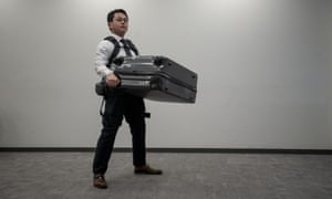 A man carries a suitcase using Panasonic's Power Assist Suit ahead of the 2020 Games.