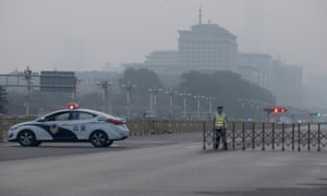 A traffic warden and police vehicle block the road leading to Tiananmen Square.