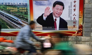 People ride past a poster featuring President Xi Jinping in Beijing
