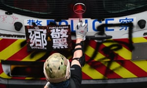 A protester spray paints graffiti on a police van