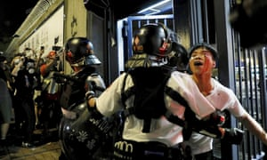 A man is taken away by policemen after attacked by protesters outside Kwai Chung police station in Hong Kong.
