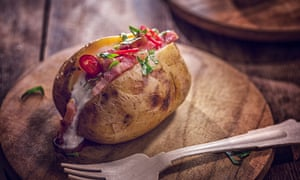 A baked potato with sour cream, bacon and chilli.