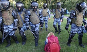 Riot police move past a young woman in Ilyinsky Park on Saturday.