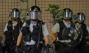 Riot police stand guard on the fringes of a demonstration