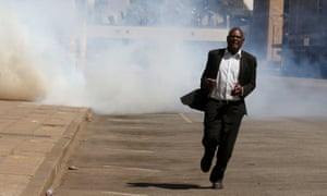 A man flees from teargas during clashes in Harare.