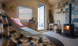 The St Aidan hut's cosy interior with logburner and sofabed in view. Alnmouth, Northumberland, UK