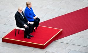 Boris Johnson and Angela Merkel sit for the national anthems
