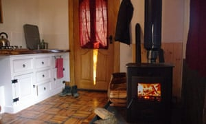 Cabin interior of kitchen area and logburner at the Bulworthy Project, Devon, UK.