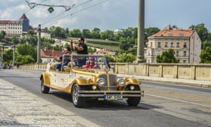 Tourists take photos as they ride in a 'Prague old car'