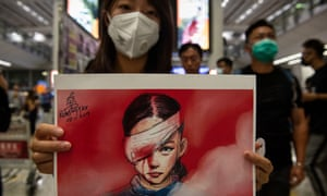 A woman holds a placard with a drawing depicting an injured protester