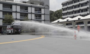 An anti-riot vehicle equipped with water cannon sprays water on a dummy during a demonstration in Hong Kong on Monday.