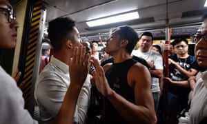 Protesters prevent the doors of a MTR underground train from closing at Fortress Hill station in Hong Kong.