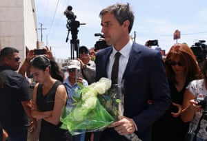 Beto O'Rourke holds a flower bouquet while arriving to the funeral services for shooting victim Ivan Filiberto Manzano.