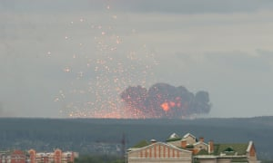 Flames and debris rise from the ammunition depot on fire.