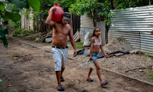 Victor Funes and his daughter Patricia carrying water in Nejapa, El Salvador