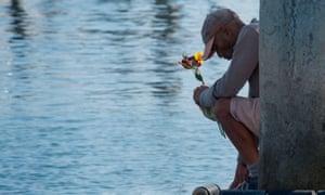 A former Truth Aquatics crewman, James Miranda, prays and drops flowers into the water at the moorings where the boat was based in Santa Barbara, California.