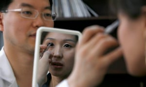 """Korean plastic surgeon Kim Byung-gun demonstrates """"double eyelid"""" surgery for a patient during a consulting session in his clinic in Shanghai in 2007."""